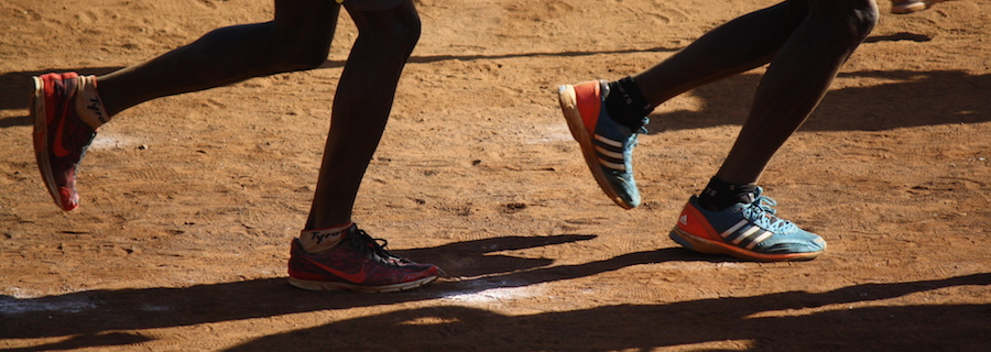 The shoes of two Kenyan runners on a dirt track