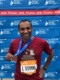 Shyam Biswal holding a finisher's medal at the 2018 Chicago Marathon
